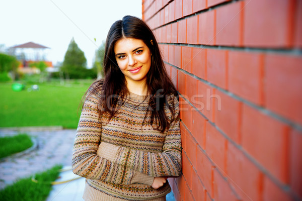 Beautiful happy woman leaning on the brick wall Stock photo © deandrobot