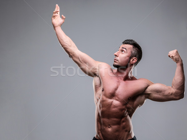 Bodybuilder posing over gray background Stock photo © deandrobot