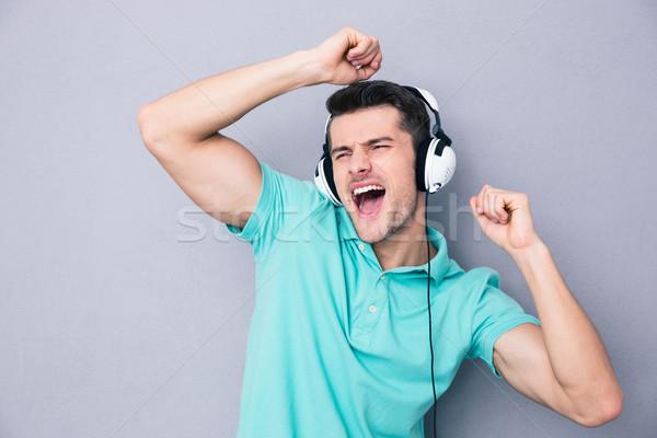 Young man singing in headphones Stock photo © deandrobot