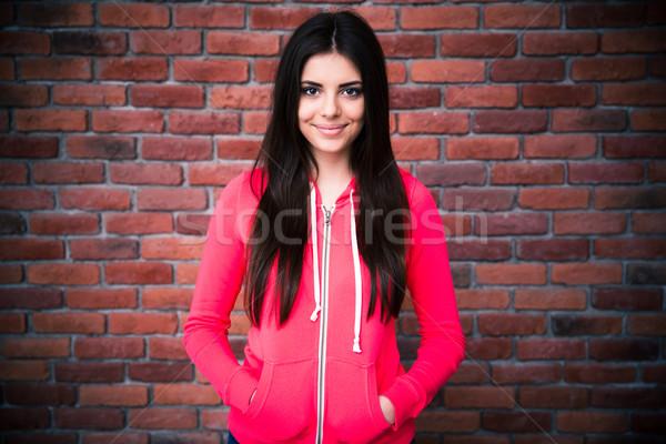 Portre kadın tuğla duvar bakıyor kamera Stok fotoğraf © deandrobot