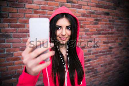 Happy young sportive woman looking on smartphone Stock photo © deandrobot