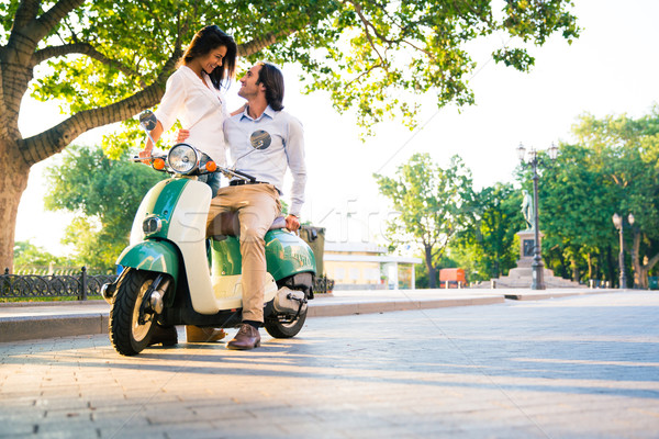 Happy beautiful couple flirting on scooter Stock photo © deandrobot