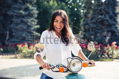 Young cheerful woman riding vintage scooter Stock photo © deandrobot