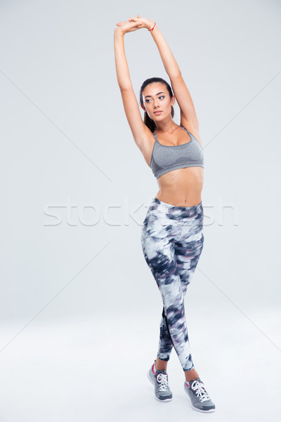 Beautiful sports woman stretching hands Stock photo © deandrobot
