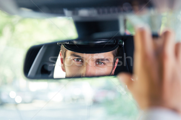 Male chauffeur looking at his reflection in a mirror Stock photo © deandrobot