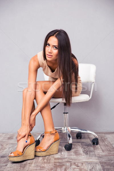Woman sitting on chair with pain in leg  Stock photo © deandrobot