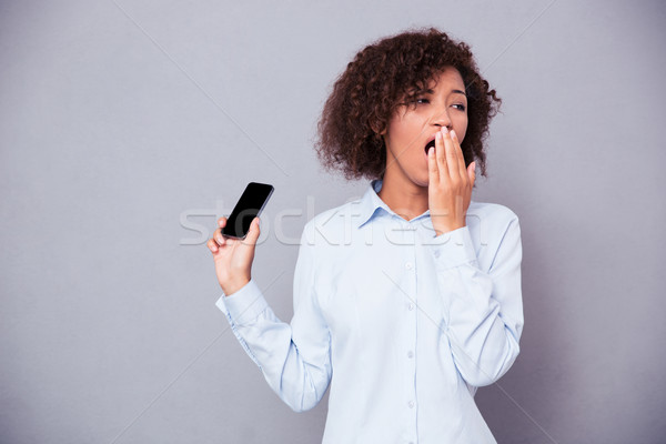 Afro american woman yawning while holding smartphone Stock photo © deandrobot