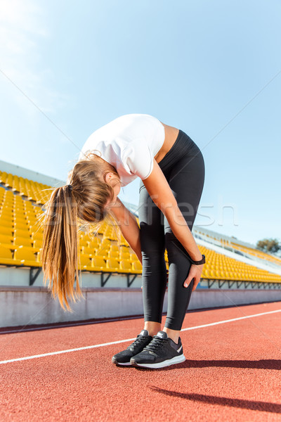 Stock photo: Woman warming up at stadium