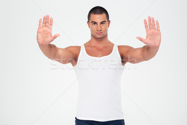 Strong man showing stop gesture with palms Stock photo © deandrobot