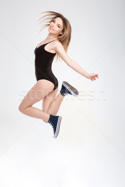Young carefree joyful girl enjoying jumping Stock photo © deandrobot