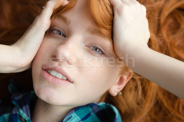 Closeup of cute girl lying on floor with tousled hair Stock photo © deandrobot