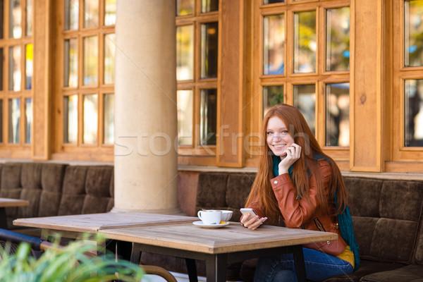 Atrakcyjny wesoły kobieta posiedzenia zewnątrz Zdjęcia stock © deandrobot