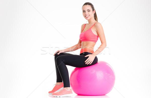 örömteli vonzó fiatal sportoló ül rózsaszín Stock fotó © deandrobot