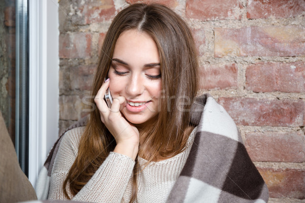 Happy woman in warm plaid talking on the phone Stock photo © deandrobot