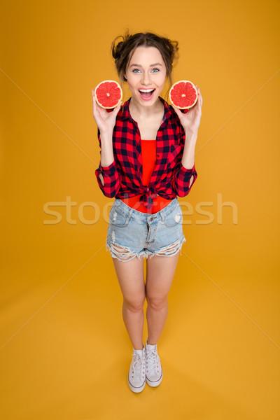 Derűs csinos fiatal nő tart kettő grapefruit Stock fotó © deandrobot