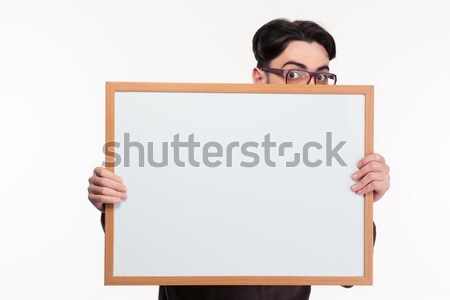 Young man peeping from blank board Stock photo © deandrobot