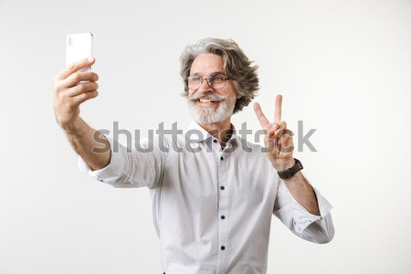 Handsome african american man showing biceps and making selfie Stock photo © deandrobot