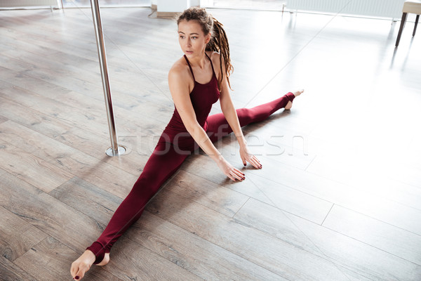Concentrated beautiful young woman doing twine on the floor  Stock photo © deandrobot