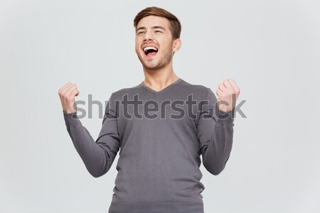 Happy excite young man screaming and celebrating his succcess Stock photo © deandrobot