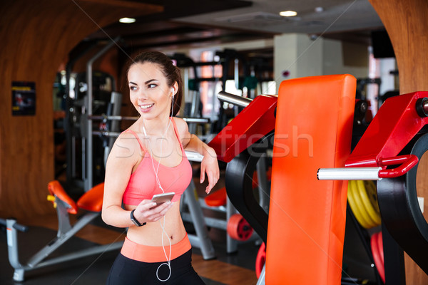 Cheerful sportswoman listening to music from mobile phone in gym Stock photo © deandrobot