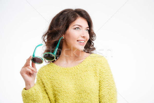 Smiling woman holding sunglasses and looking away Stock photo © deandrobot