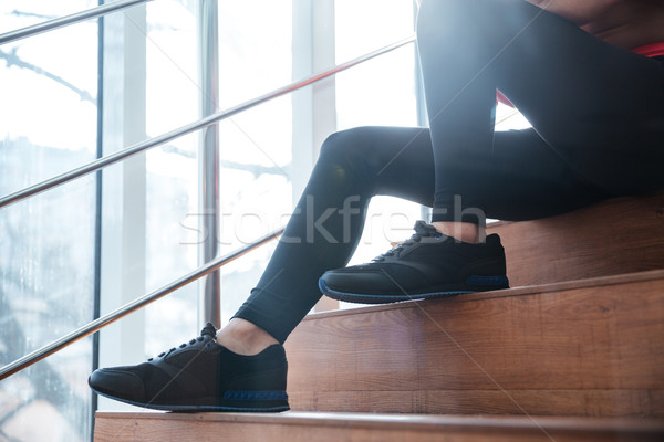 Legs in black leggings of young sportswoman sitting on stairs  Stock photo © deandrobot