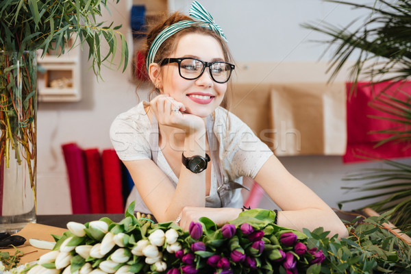 Attractive smiling young woman florist working in flower shop Stock photo © deandrobot