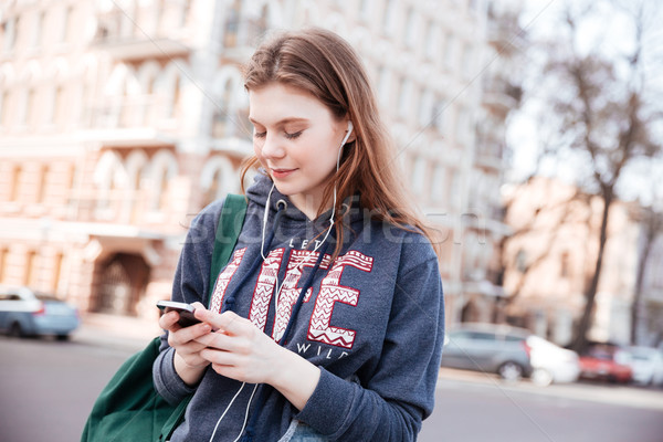 Woman listening to music and using cell phone on street Stock photo © deandrobot