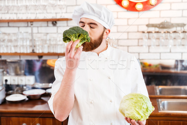 Happy bearded chef cook smelling fresh broccoli Stock photo © deandrobot