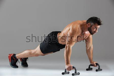 Full length of serious young man athlete doing push ups Stock photo © deandrobot