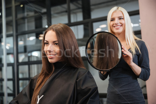 Hairstylist making women's haircut to an attractive woman Stock photo © deandrobot