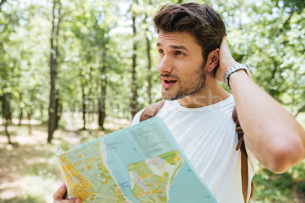 Man with backpack standing in forest and using map Stock photo © deandrobot