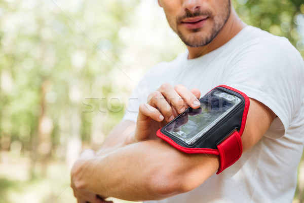 Stock photo: Closeup of young man athlete using mobile phone in handband
