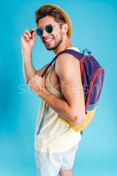 Smiling young man in hat and sunglasses with backpack Stock photo © deandrobot