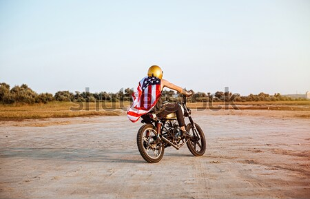 Side view of man in american flag cape driving motorcycle Stock photo © deandrobot