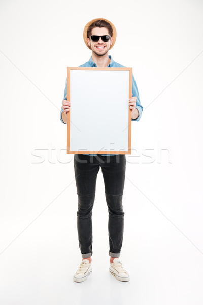 Smiling young man in hat and sunglasses holding blank whiteboard Stock photo © deandrobot
