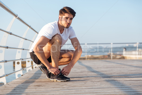 Sportsman laces his sneakers on wooden terrace Stock photo © deandrobot