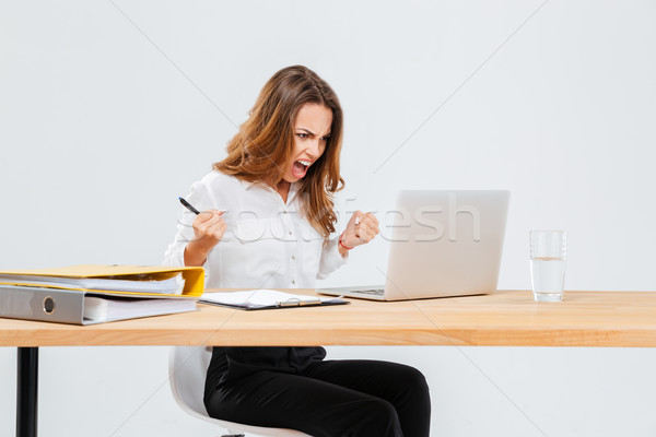 Angry young businesswoman using laptop and shouting Stock photo © deandrobot