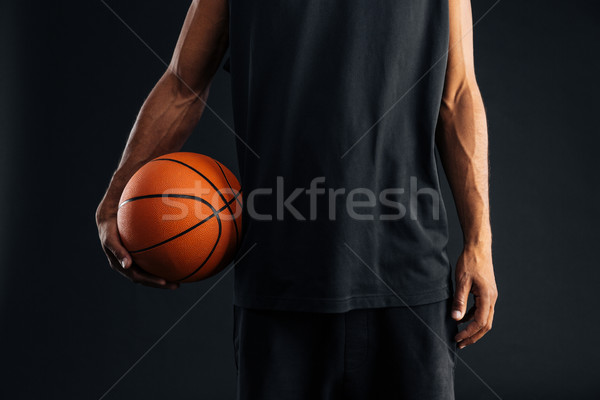 Cropped image of an african basketball player holding ball Stock photo © deandrobot