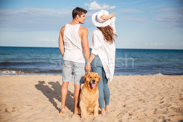 Couple stading and holding hands near their dog on beach Stock photo © deandrobot