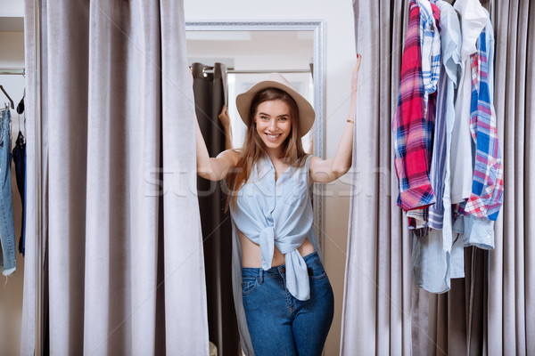 Cheerful pretty young woman trying on clothes in fitting room Stock photo © deandrobot