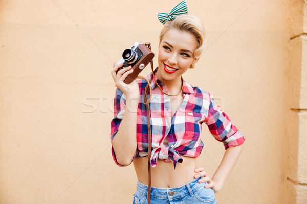 Cheerful charming pinup girl in yellow dress using vintage camera Stock photo © deandrobot