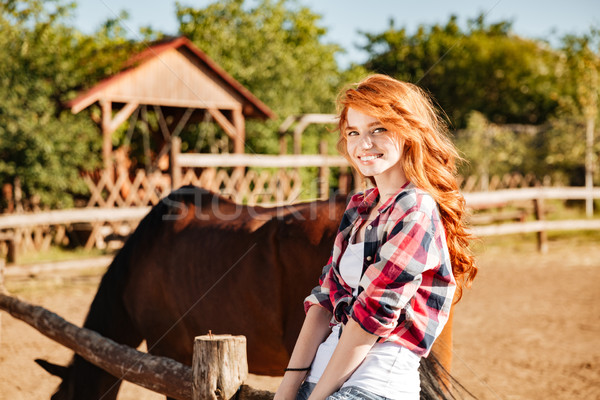 Cheerful attractive young woman cowgirl with horse in village Stock photo © deandrobot