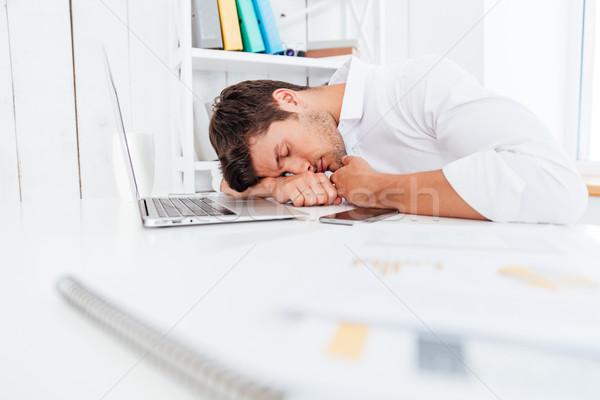Exhausted fatigued young businessman sleeping on the table Stock photo © deandrobot