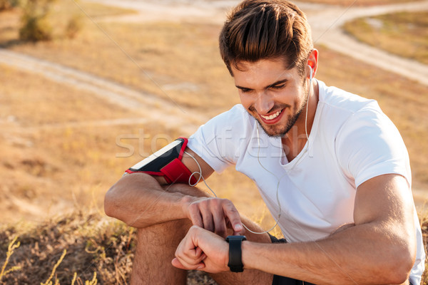 Handsome young sportsman sitting and using smart watch Stock photo © deandrobot