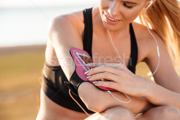 Woman runner listening to music with mobile phone in armband Stock photo © deandrobot