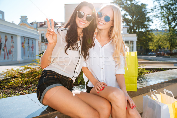 Two women resting on a bench together after shopping Stock photo © deandrobot