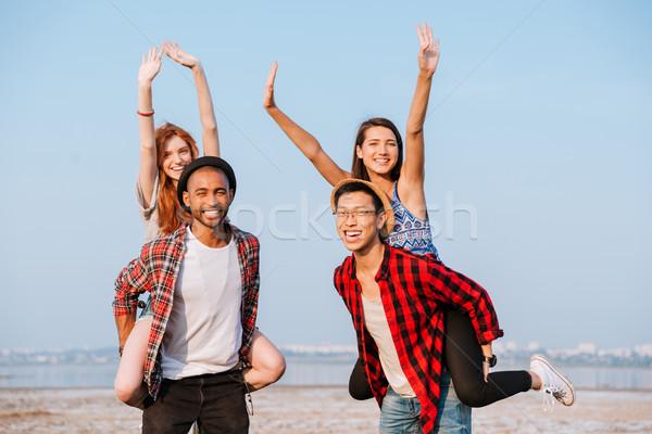 Two cheerful young men holding girlfriends on their backs outdoors Stock photo © deandrobot