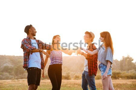 Cheerful young friends drinking beer and soda outdoors Stock photo © deandrobot