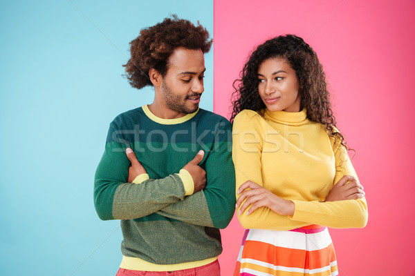 Couple standing with arms crossed and looking at each other Stock photo © deandrobot